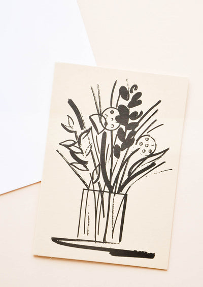 A white envelope and tan greeting card featuring an illustrated floral arrangement in black.