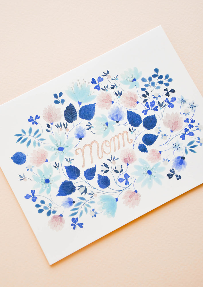 "2: Greeting card with blue floral print frame around ""Mom"" printed in copper text"