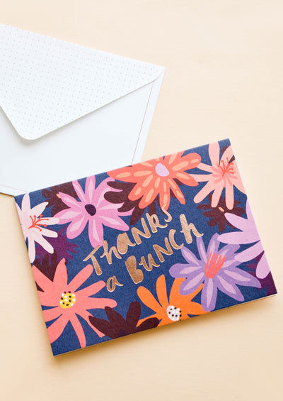 "Greeting card with colored daisies and foil stamped text ""Thanks a bunch"", with white envelope"