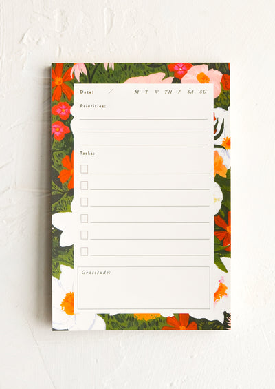 A notepad with days of the week, priorities, tasks, and gratitude.