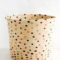 2: A round raffia hamper in natural with colorful dashes throughout.