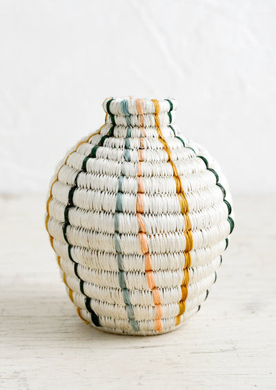 A decorative vase made from woven sweetgrass in white with vertical pastel stripes.