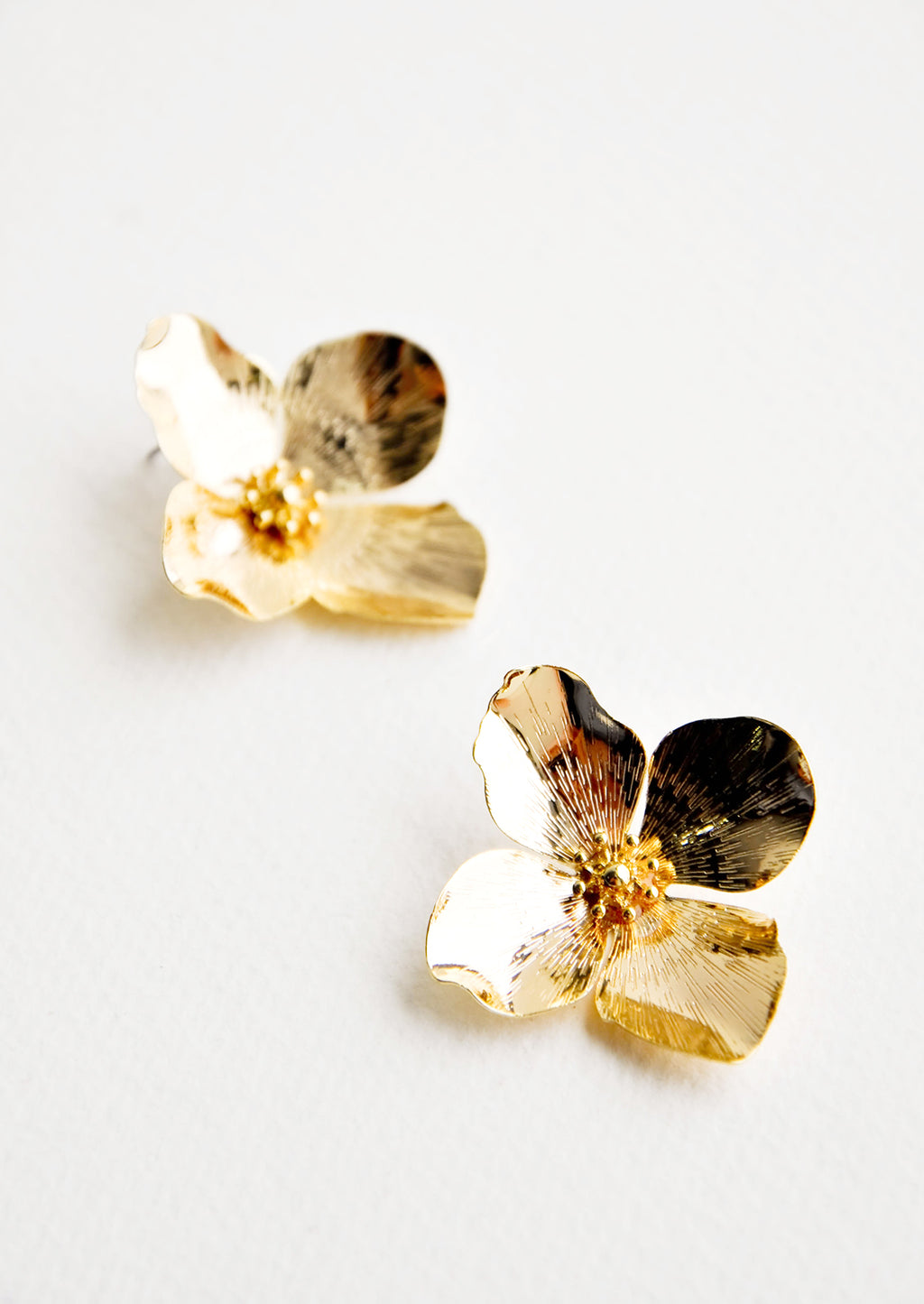 1: Shiny gold flower shaped earrings with four petals.