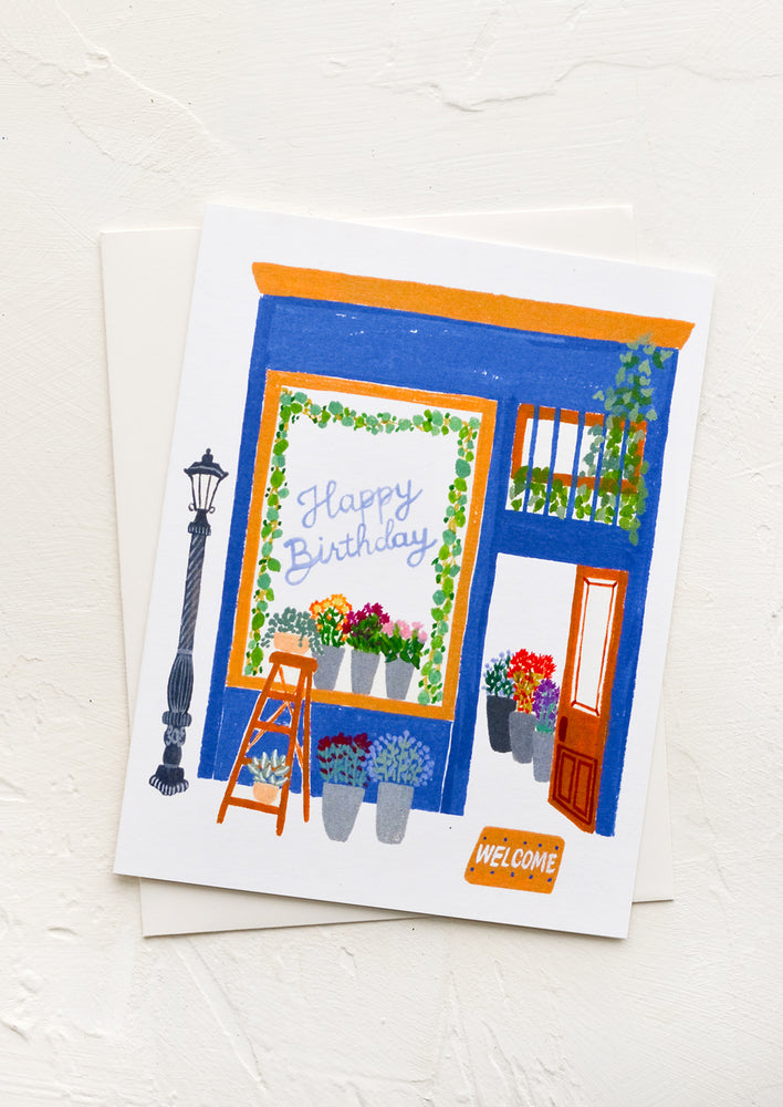 "1: A greeting card with image of flower shop with ""Happy birthday"" written in window."