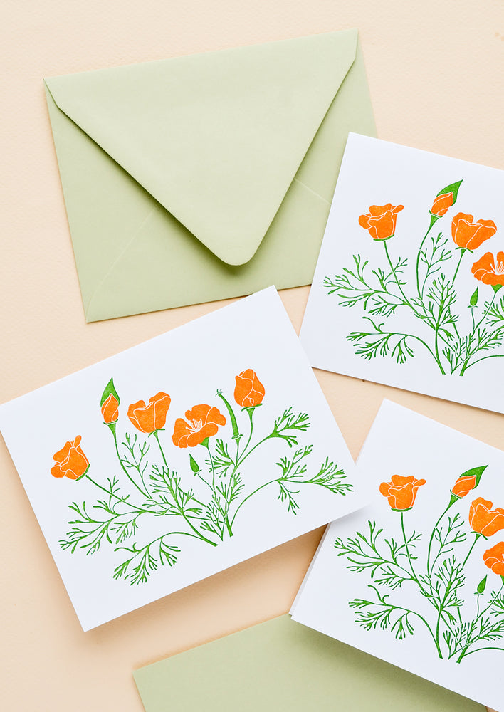 1: A set of white greeting cards with orange poppy flowers printed on front, paired with pastel green envelopes.