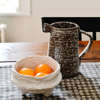 White: Tabletop scene with ceramic pitcher and white paper mache bowl with tangerines