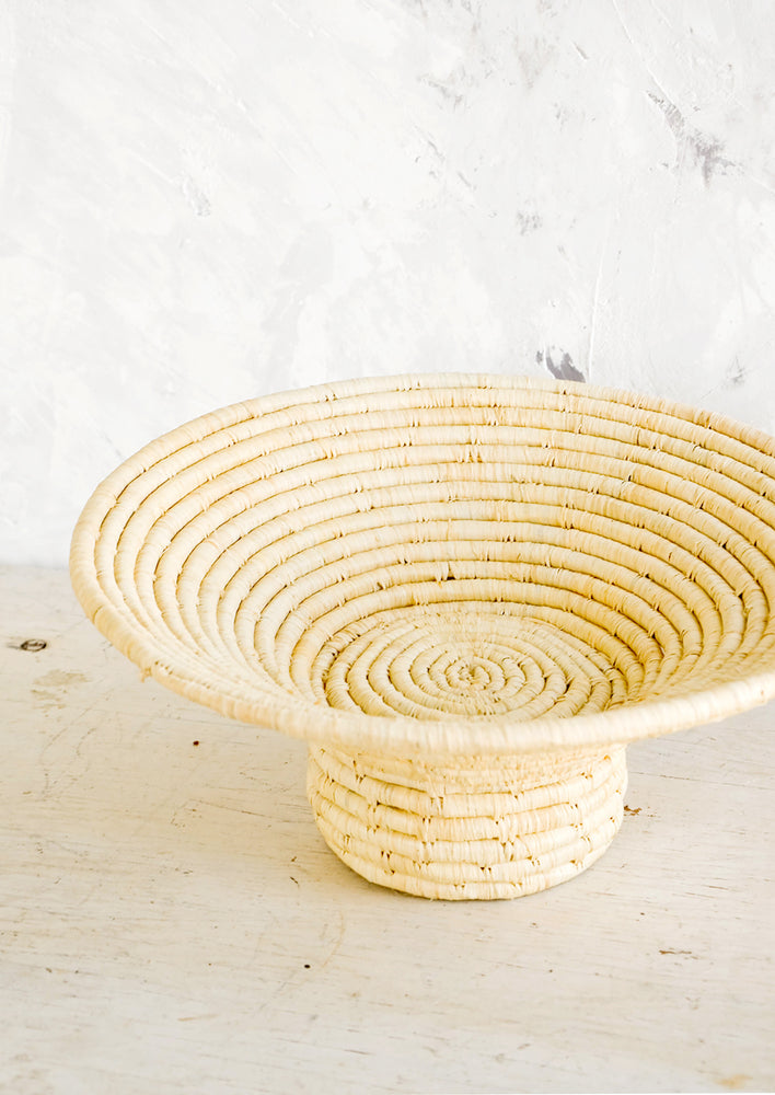 1: Footed pedestal bowl made from natural woven raffia, sitting on a table