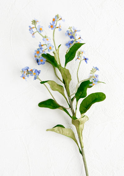 A realistic looking faux flower stem made to look like forget me not.