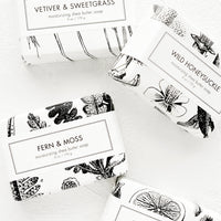 1: Four bars of soap in black & white botanical graphic packaging.