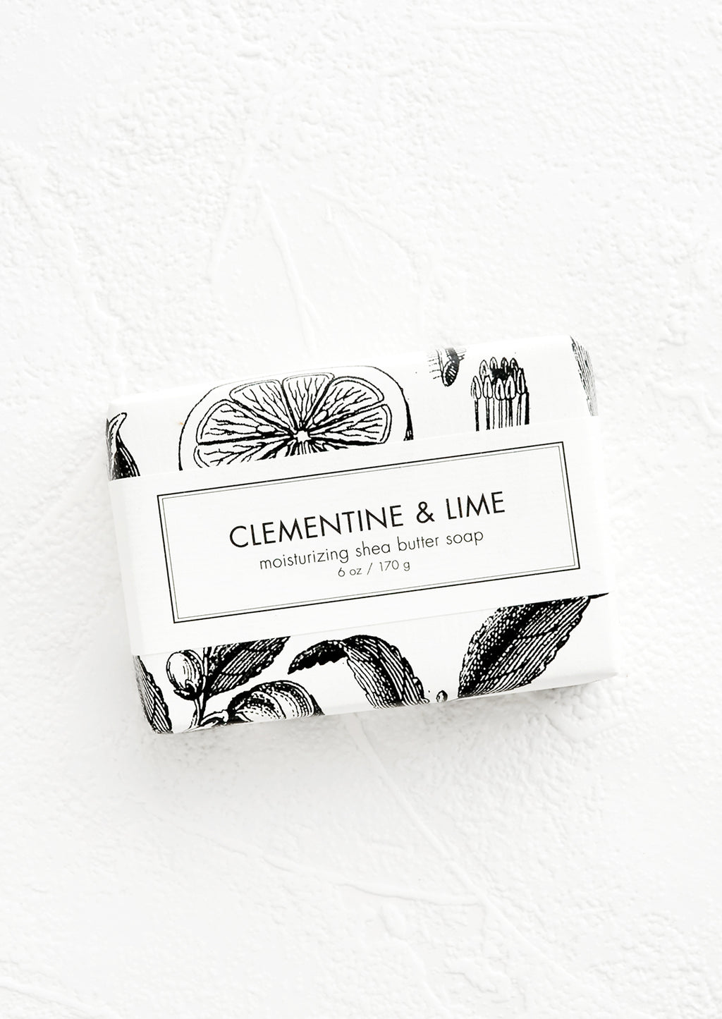 Clementine & Lime: A bar of soap in black & white botanical graphic packaging.