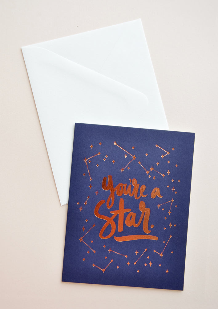 "1: Navy blue notecard with metallic copper constellation decoration and the text ""You're A Star"", with white envelope."