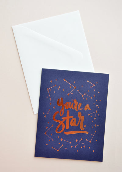 "Navy blue notecard with metallic copper constellation decoration and the text ""You're A Star"", with white envelope."
