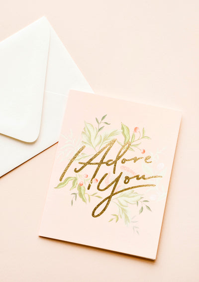 "Pink greeting card with green leaf pattern and ""I Adore You"" written in gold foil. Shown with white envelope."