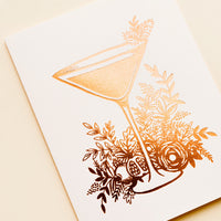 2: A pale pink greeting card with an image in copper foil of a martini glass surrounded by greenery.