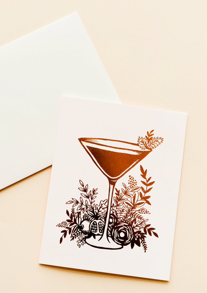 1: An off-white envelope with a pale pink greeting card featuring an image in copper foil of a martini glass surrounded by plant life.