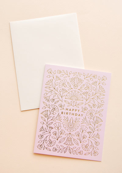 "An off-white envelope and a pale purple card with gold foil floral pattern and the words ""happy birthday"" at center."