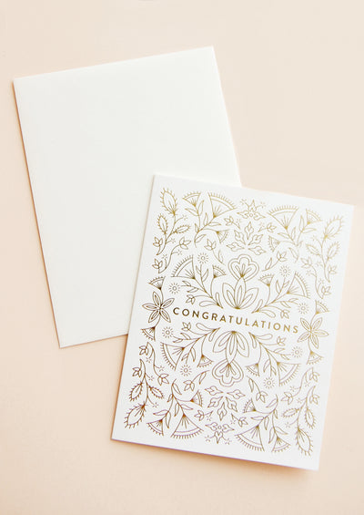 "Notecard with intricate gold metallic floral design all over and the text ""Congratulations"", with white envelope."