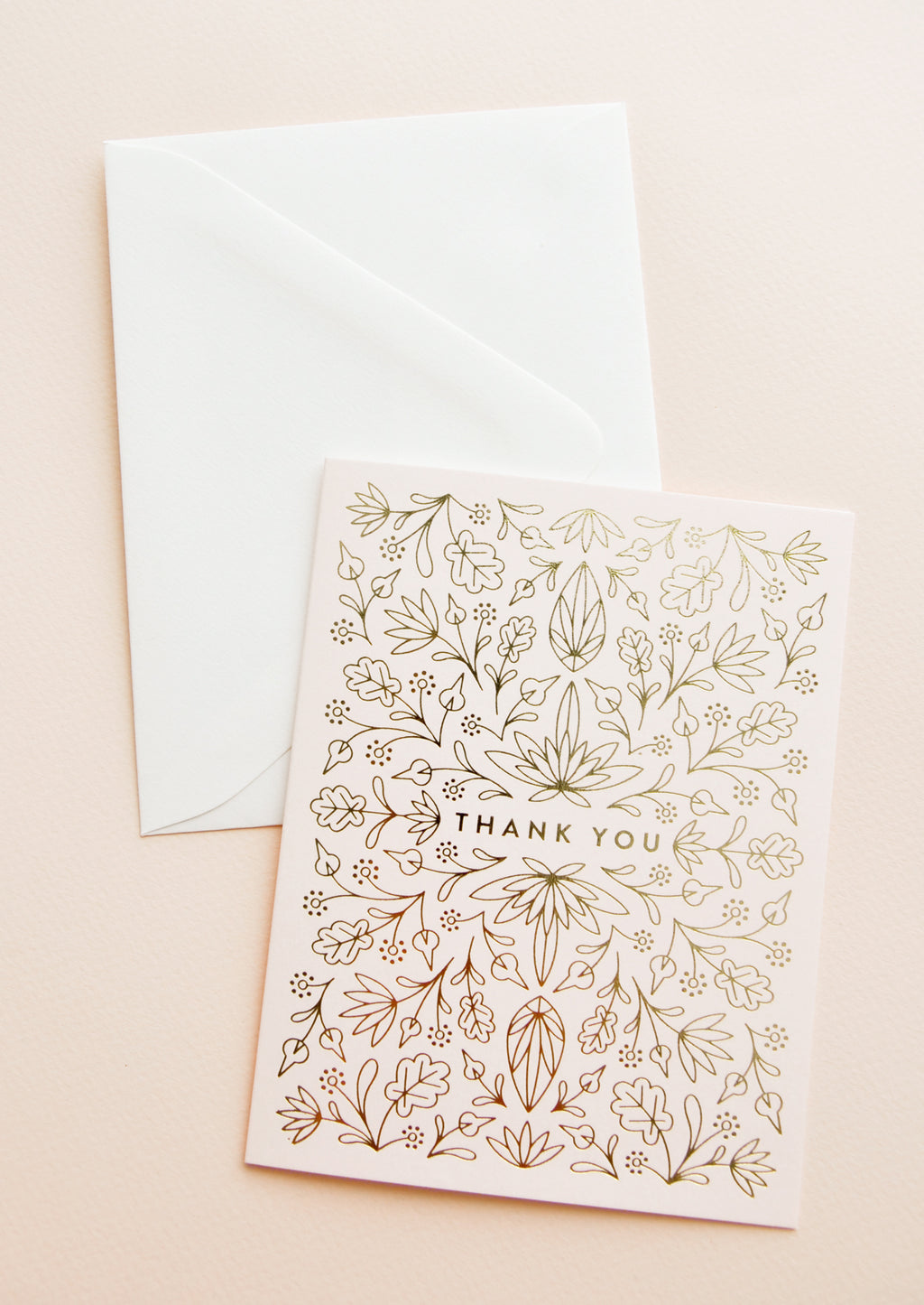 "2: Pale pink notecard featuring intricate gold metallic floral design all over and the text ""Thank You"", with white envelope."