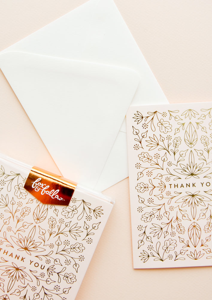 "1: Notecard set with pale pink cards featuring intricate gold metallic floral design all over and the text ""Thank You"", with white envelope."