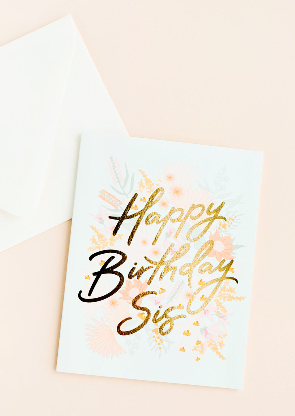 "1: A white envelope and pale blue greeting card with a pink floral motif and the words ""happy birthday sis"" in gold foil."