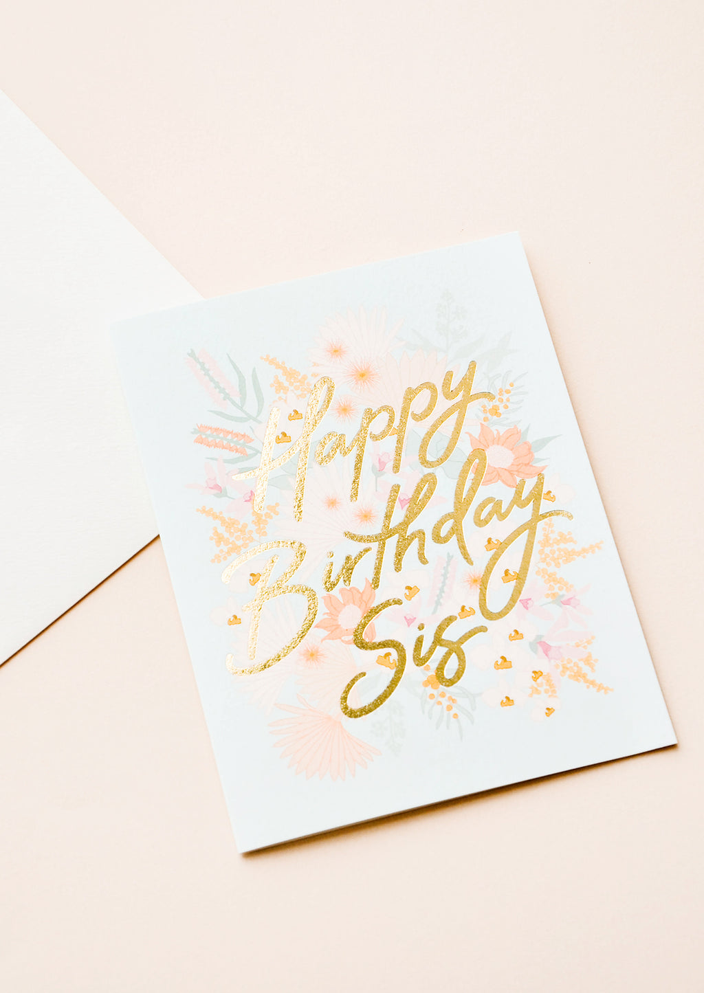 "2: A  pale blue greeting card with a pink floral motif and the words ""happy birthday sis"" in gold foil."