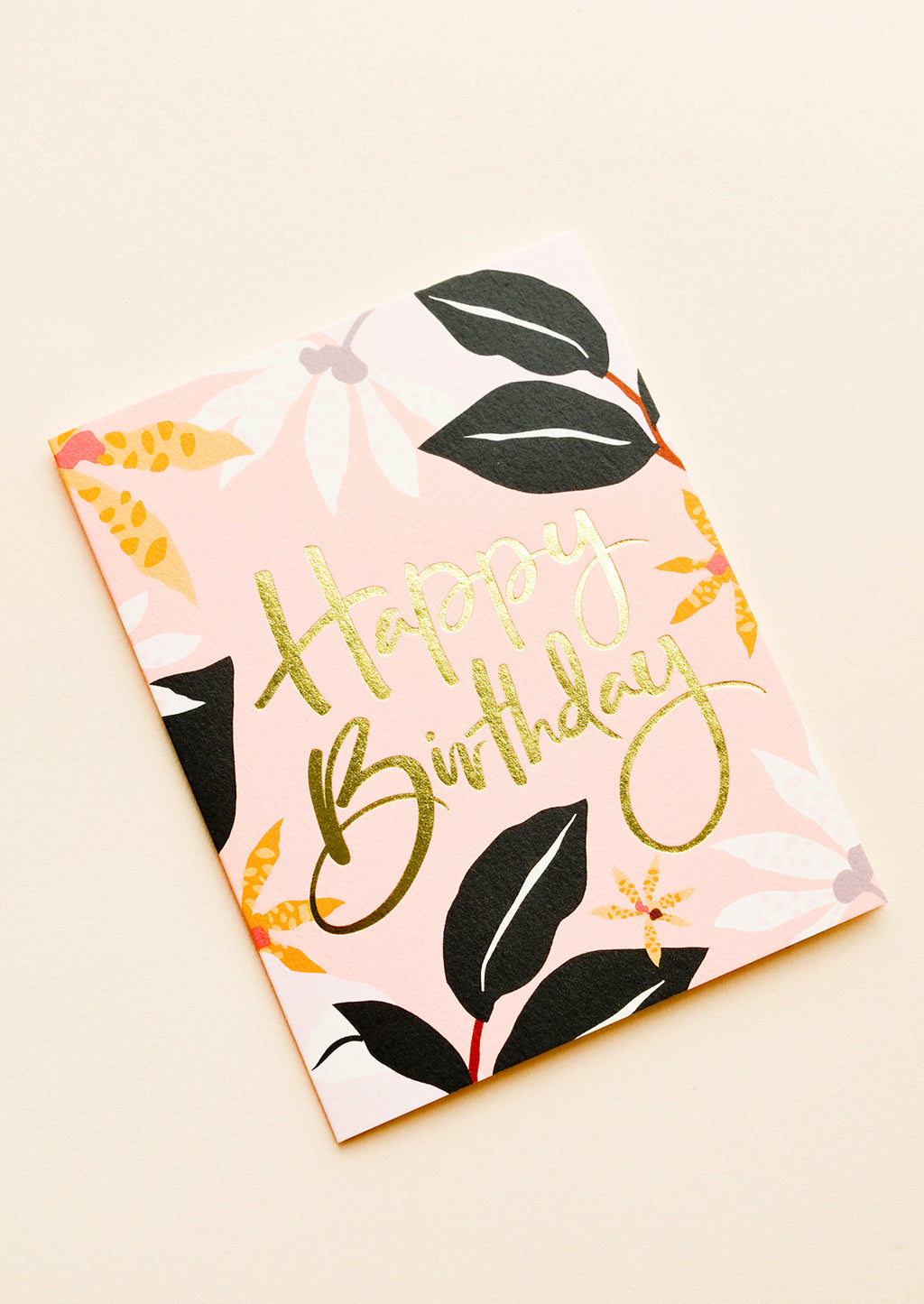 "2: A pink greeting card with black, white, and orange floral print and the words ""happy birthday"" in gold foil script."