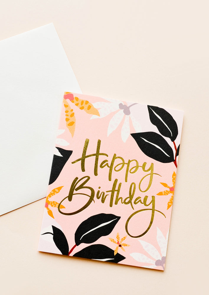 "1: A white envelope and pink greeting card with black, white, and orange floral print and the words ""happy birthday"" in gold foil script."