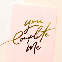 "1: Pink greeting card with ""you complete me"" written in large gold script. Shown with white envelope."