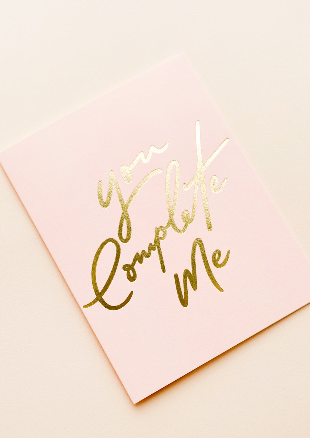 "2: Close up of gold foil ""You Complete Me"" text."