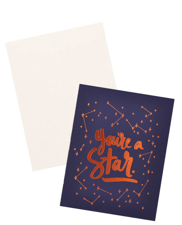"2: Navy blue notecard with metallic copper constellation decoration and the text ""You're A Star"", with white envelope."