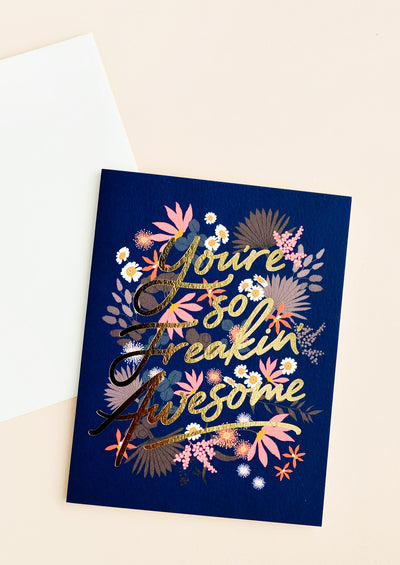 "Navy blue notecard with colorful floral decoration and the text ""You're So Freakin Awesome"" in gold foil script, with white envelope."