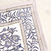 1: Tablecloth folded on a table. Features a bordered floral pattern in grey/lavender.