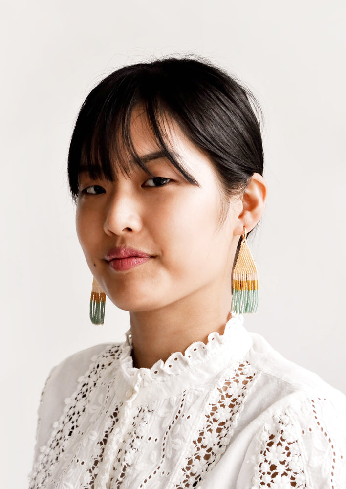 2: Model shot of woman wearing beaded earrings and white top.