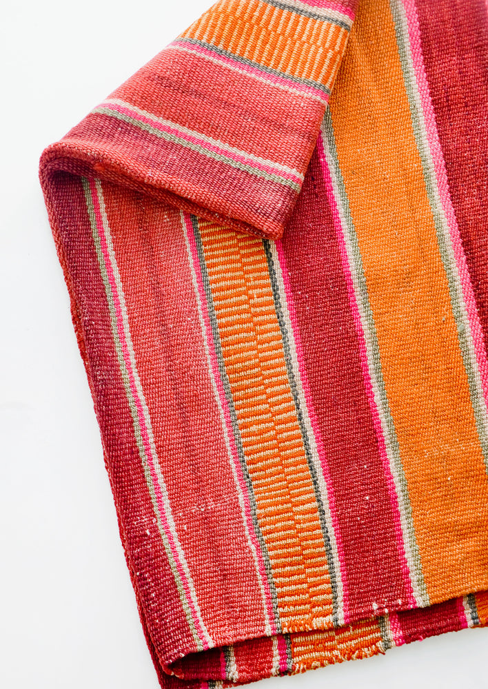 Woven textile intended for use as a rug or blanket, variegated colorful striped pattern.