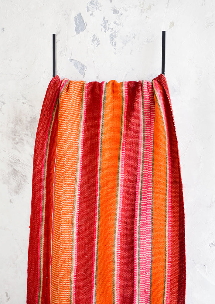 2: Colorful, striped woven textile intended for use as a rug or blanket, hung on a display ladder.