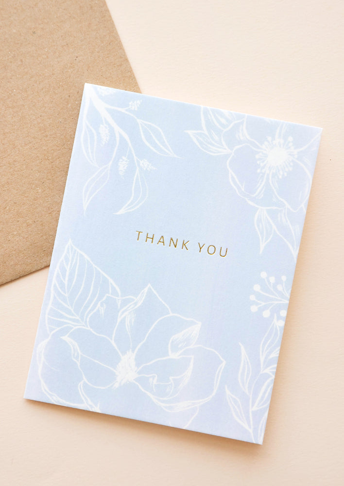 "1: Pale blue notecard with white floral decoration and the text ""thank you"", with brown envelope."