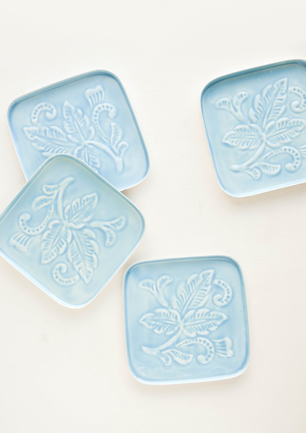 Aqua: Square coasters in blue enamel with raised floral motif