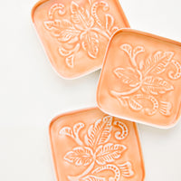 Peach: Square coasters in peach enamel with raised floral motif