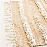 2: Close up of tan jute rug with fluffy, raised stripe detailing in ivory, featuring tasseled edges.