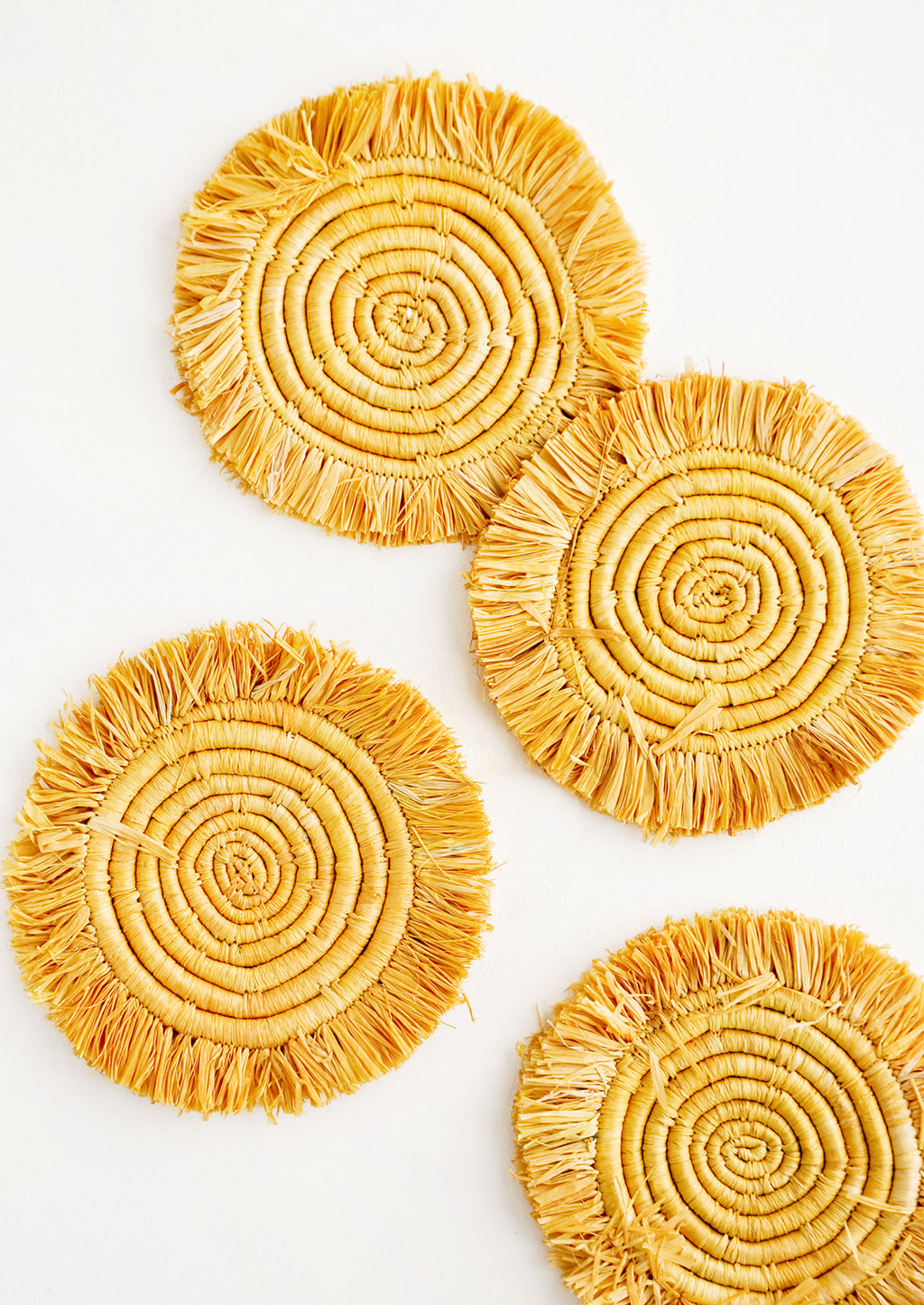 Marigold: Set of 4 Circular Raffia Coasters with Fringed Trim in Yellow