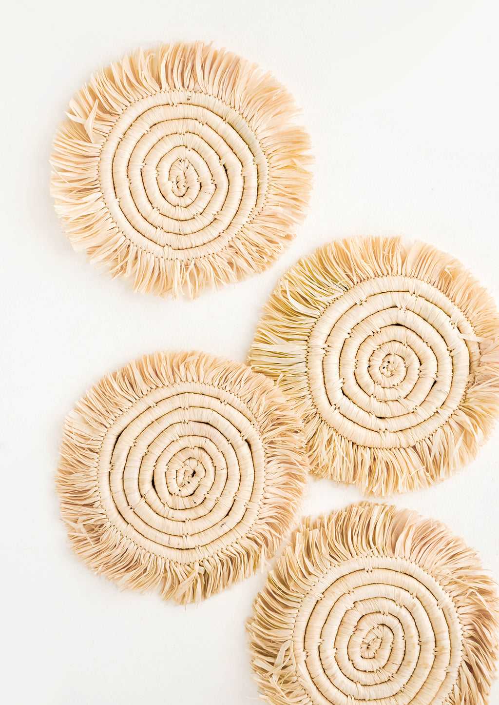 Natural: Set of 4 Circular Raffia Coasters with Fringed Trim in Natural