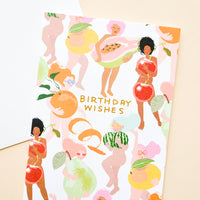 "1: Greeting card with illustrated people, covering themselves with fruit. ""Birthday Wishes"" written in orange text. Shown with white envelope."