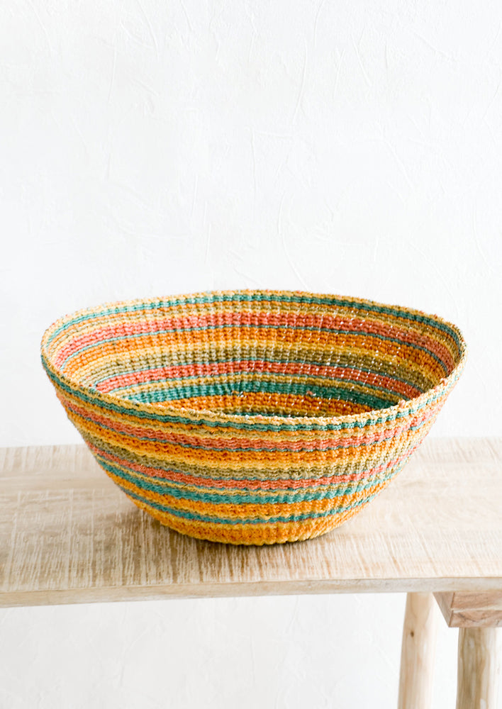 1: Colorful striped, round storage basket woven from dyed abaca grass