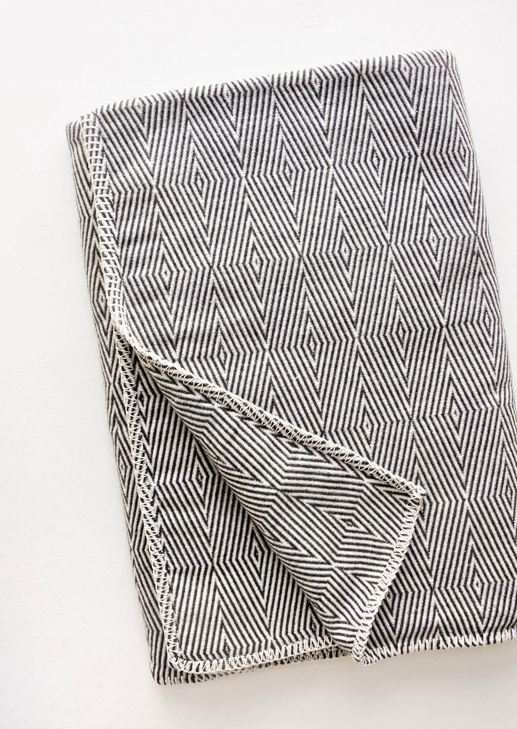 1: Cotton blanket with allover geometric diamond pattern in black and white
