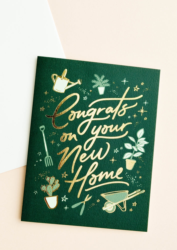 "1: A dark green greeting card with gardening illustrations and gold foil script reading ""congrats on your new home."""