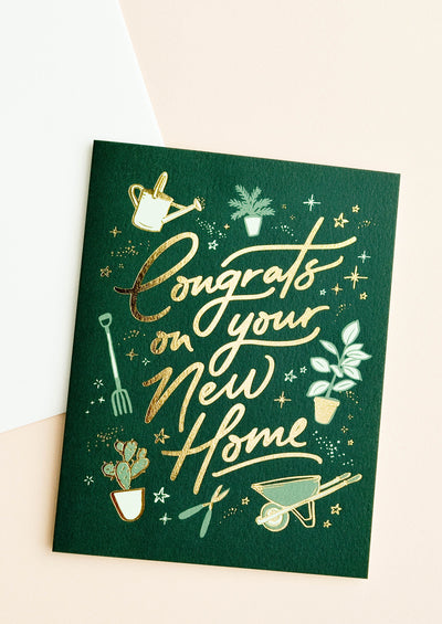 "A dark green greeting card with gardening illustrations and gold foil script reading ""congrats on your new home."""