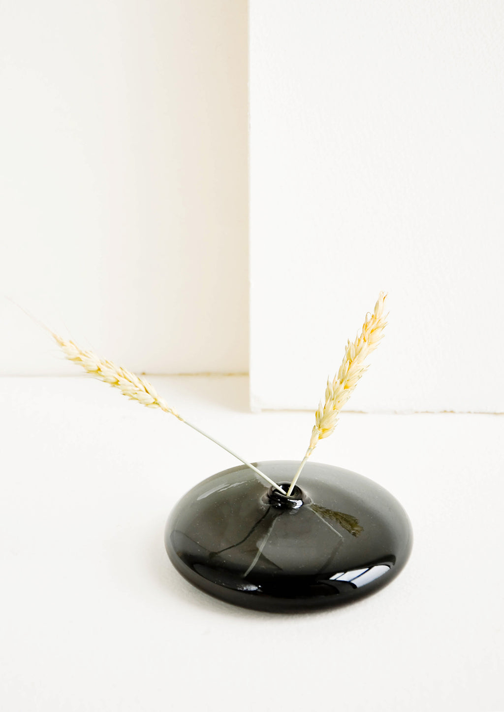 Low / Shadow: Small bud vase in translucent black glass, in a shallow flat shape displayed with decorative straw