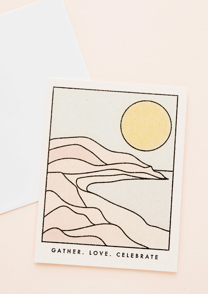 "1: Greeting card with an illustrated scene of an arid desert landscape and yellow sun, text at bottom reads ""Gather. Love. Celebrate."""