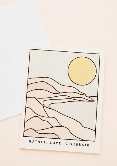 "Greeting card with an illustrated scene of an arid desert landscape and yellow sun, text at bottom reads ""Gather. Love. Celebrate."""