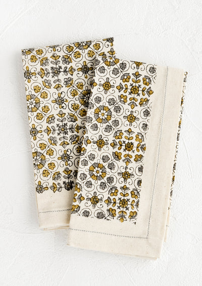 A pair of folded cotton napkins in floral print in grey and ochre.